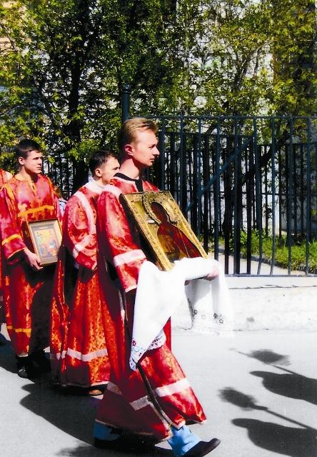 Спасенную икону Георгия Победоносца, возвращенную церкви его внуком, Георгием Алексеевичем Сергеевым, несет его правнук