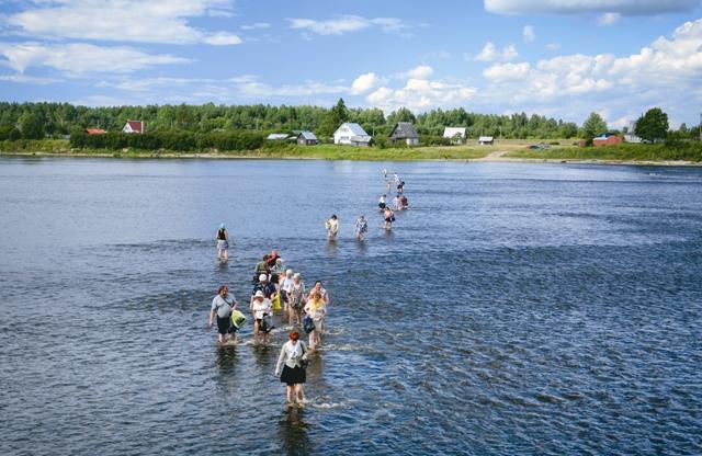 Паломники переходят вброд реку Великую
